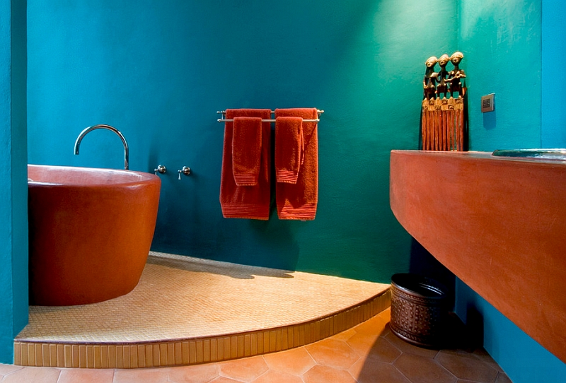 Bathtub in bright orange set against a turquoise backdrop