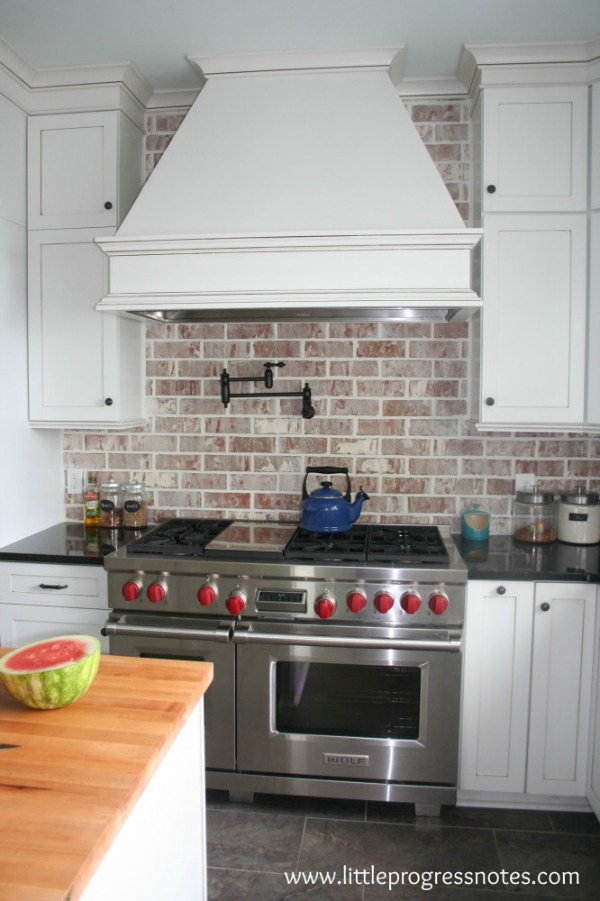 Brick backsplash white cabinets