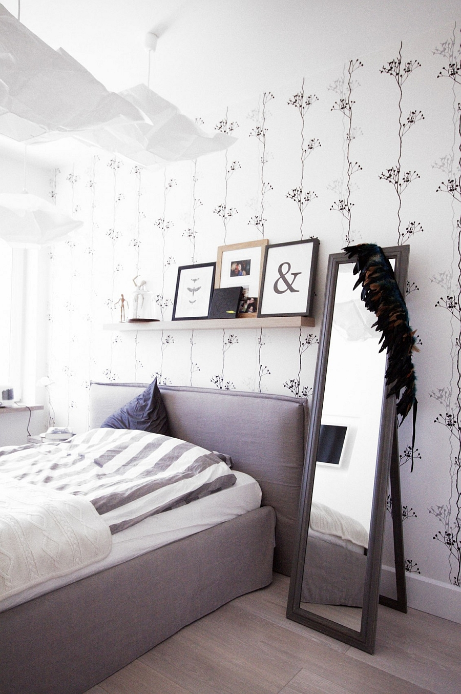 Floating shelf above the bed with framed picture collection