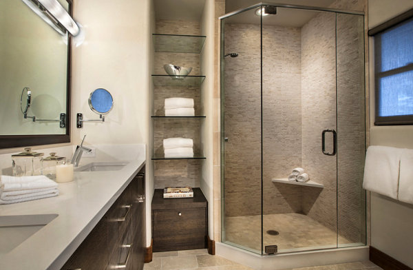 Glass shelves in a warm-toned bathroom