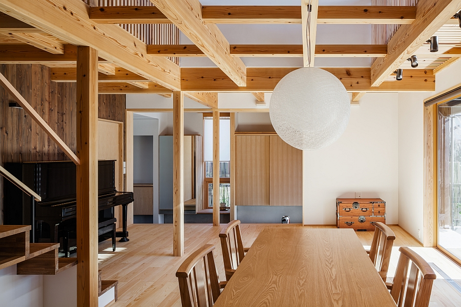 Globe pendant in white above the wooden dining table