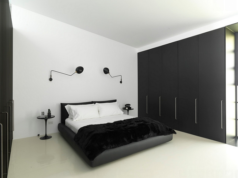 Minimal bedroom in black and white with wall sconces and Tulip side table