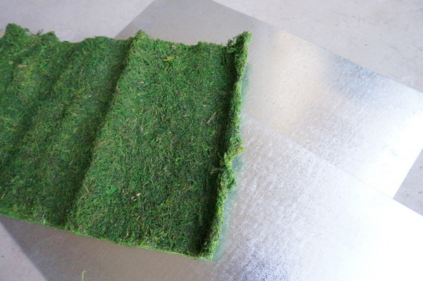 Moss and sheet metal are the supplies of choice for this outdoor DIY wall art
