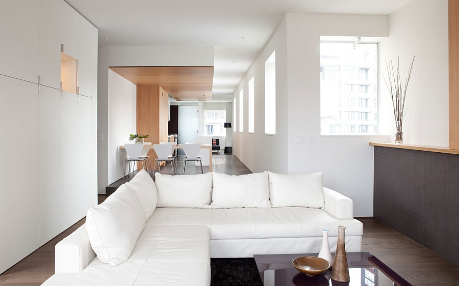 Open floor living plan and plush sofa in white Bright And Beautiful Urban Renovation Unites Two Apartments Into One