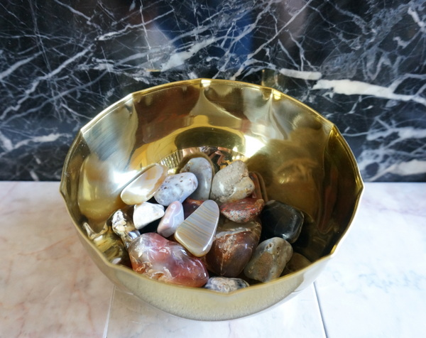 Polished pebbles in a brass bowl