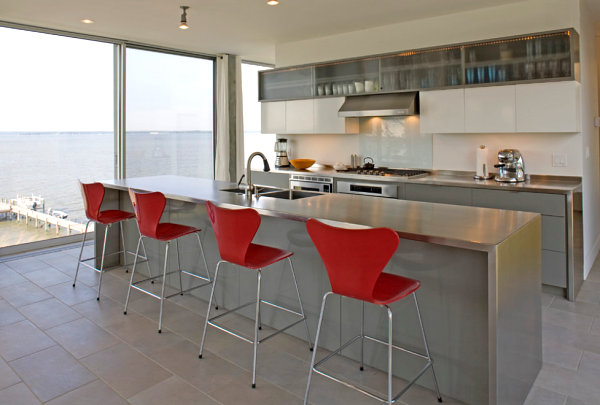 Red chairs brighten a kitchen with stainless steel countertops