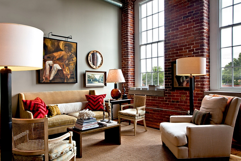 Red chevron pattern pillows complement the exposed brick wall of the eclectic home