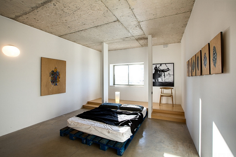 Rough concrete ceilings, walls and beams add industrial charm to the minimal bedroom