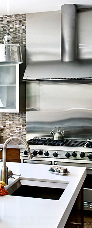 Stainless steel backsplash near the stove in a bright kitchen