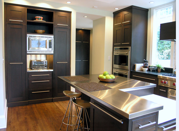 Stainless steel countertops brighten a kitchen with black cabinetry