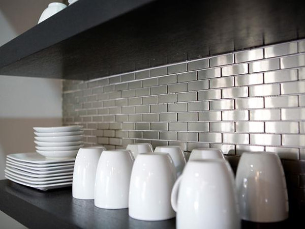 Stainless steel tile backsplash behind open shelving