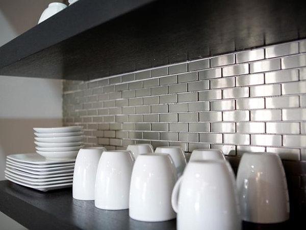 Stainless steel tile backsplash behind open shelving