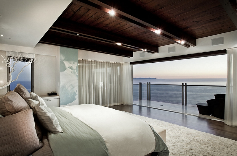 Stunning bedroom uses sheer curtains to add to the dramatic ocean views outside!