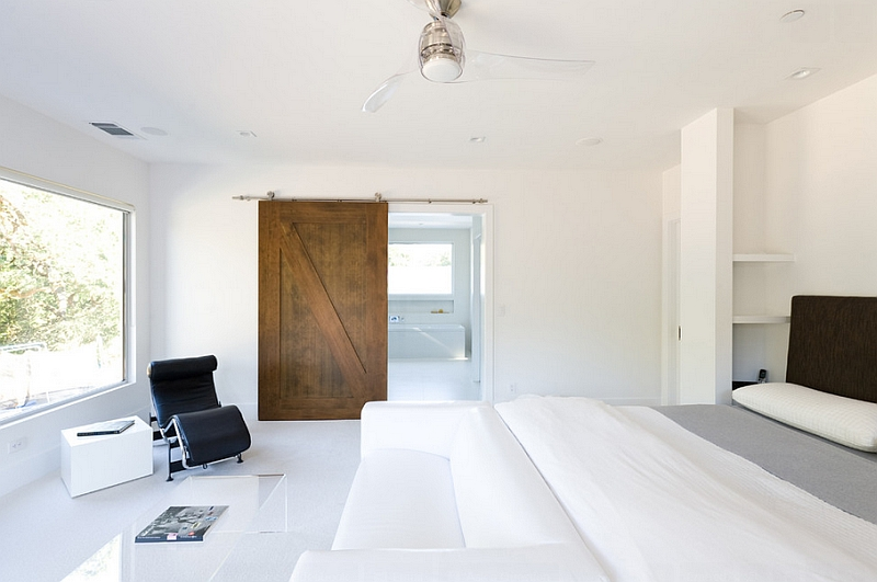 Use of barn door adds warmth to the minimalist room in white