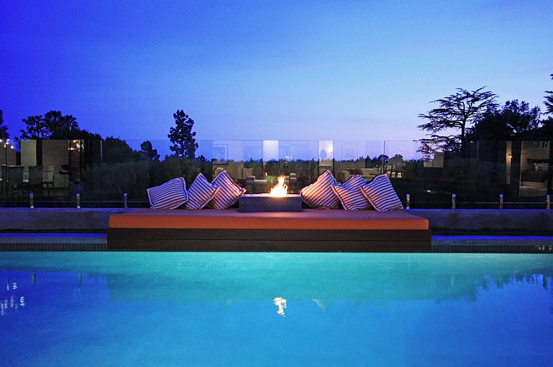 An outdoor bed next to the pool and the fireplace