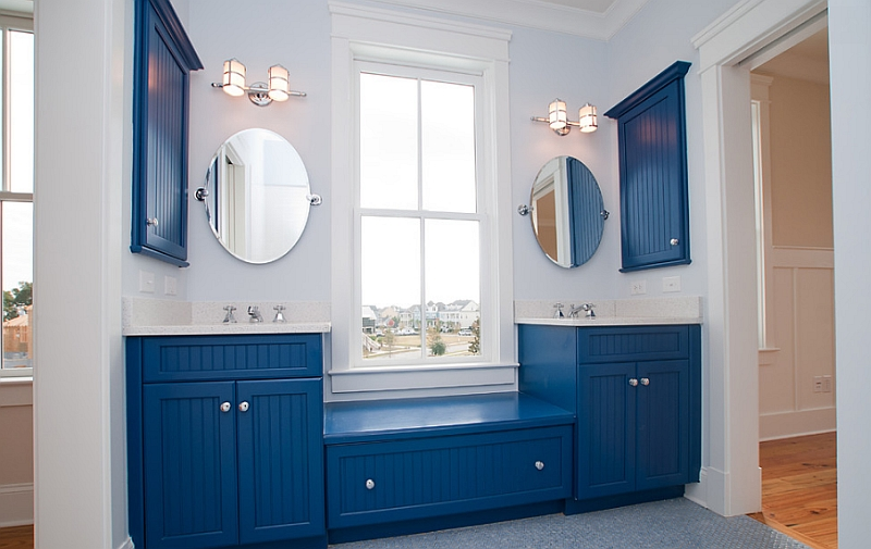 Bathroom cabinets in blue give the space an eclectic appeal