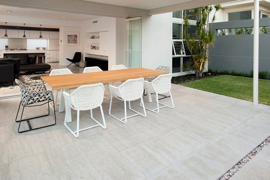 Beautiful dining space with large wooden table with white chairs