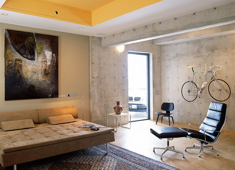 Concrete walls and the wall-mounted bicycle give the room an industrial edge