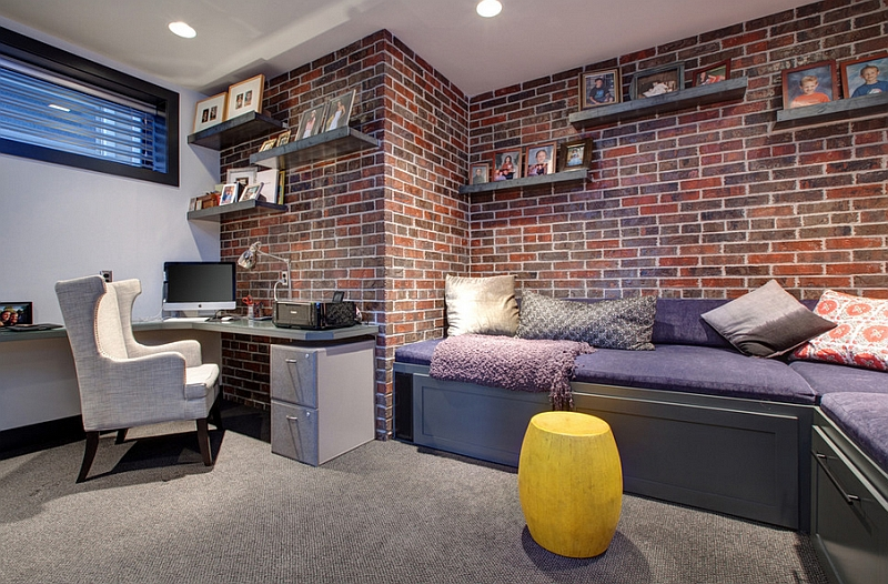 Contemporary basement home office with a brick wall