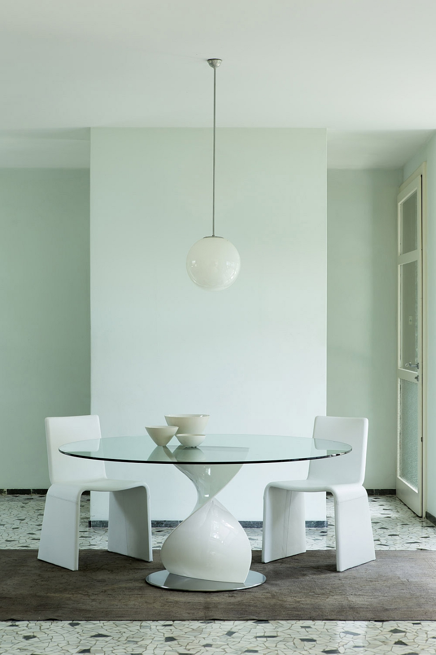 Contemporray dining table with white sculptural base and glass top