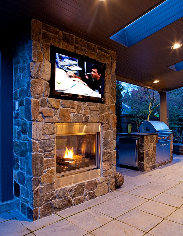 Double-sided fireplace with wall mounted television in the patio