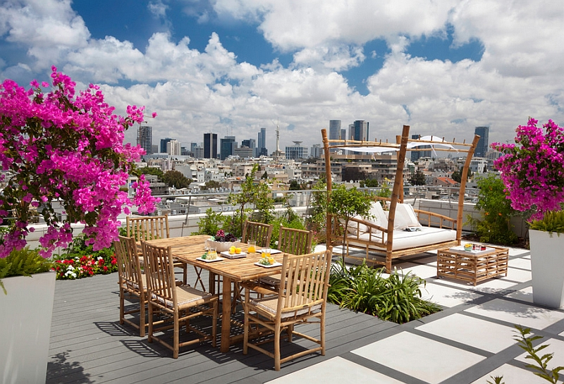 Fabulous rooftop deck with a teakwood outdoor bed that exudes organic charm
