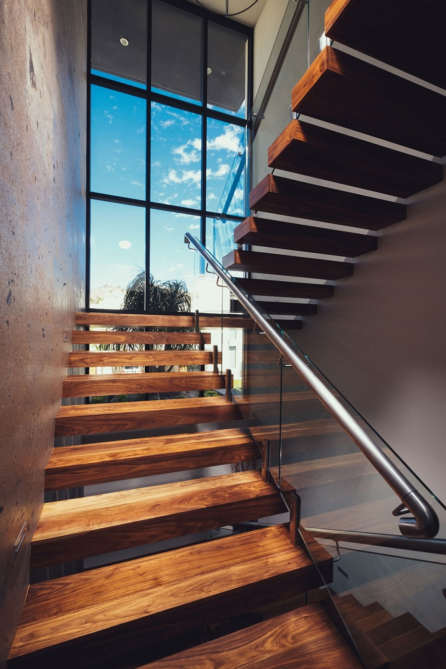 Floating Wooden Stairs With A Glass And Steel Railing
