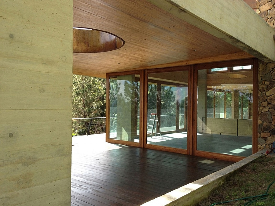 Glass doors connect the interior with the wooden deck