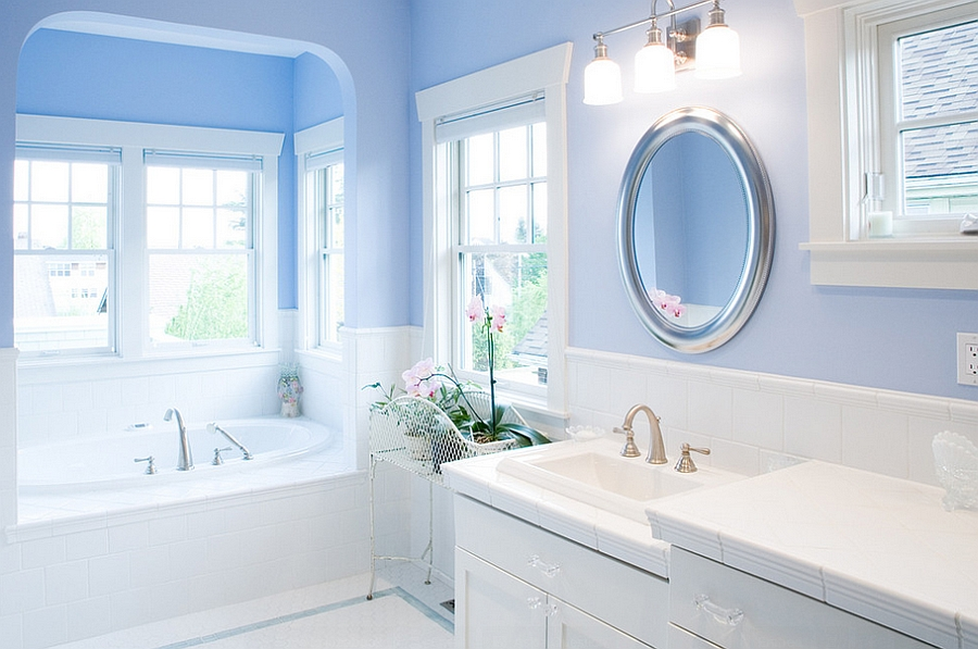 Gorgeous bathroom in blue and white with round mirror above the sink
