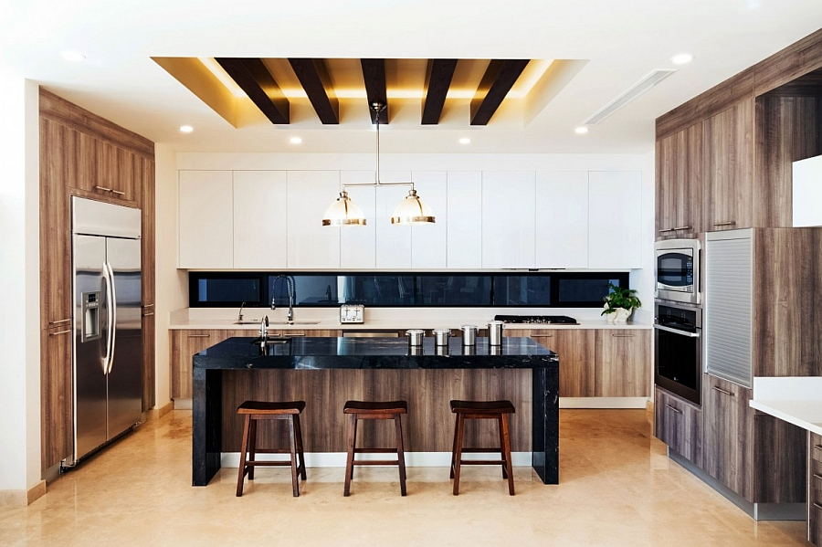 Gorgeous modern kiitchen with white cabinets and an island in black stone