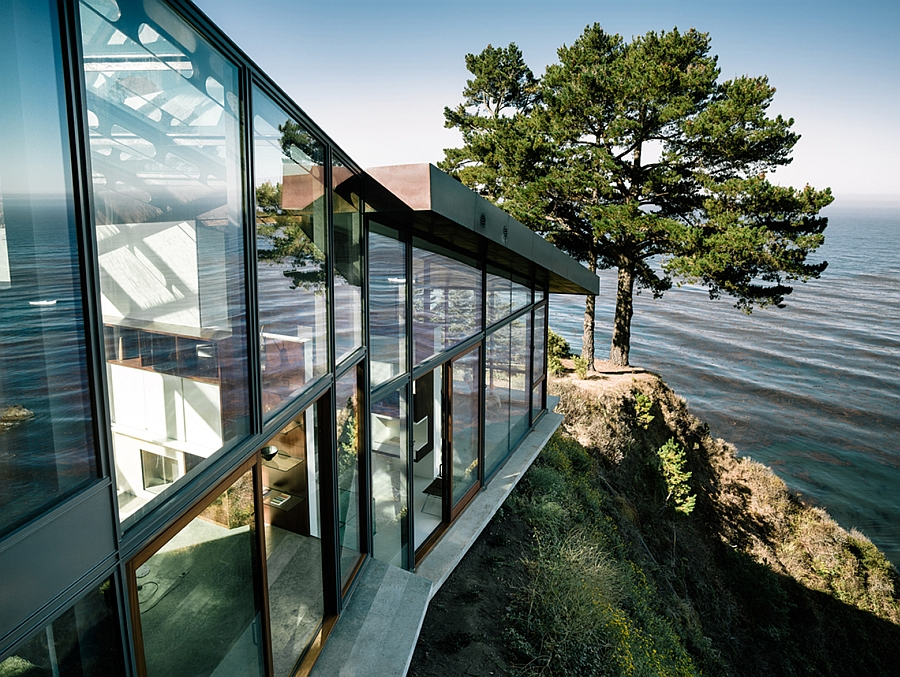 Large glass windows on the side of the contemporary home atop a cliff