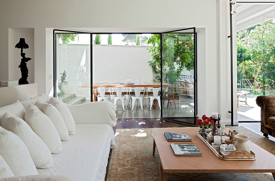 Living space in white connected to outdoor dining area