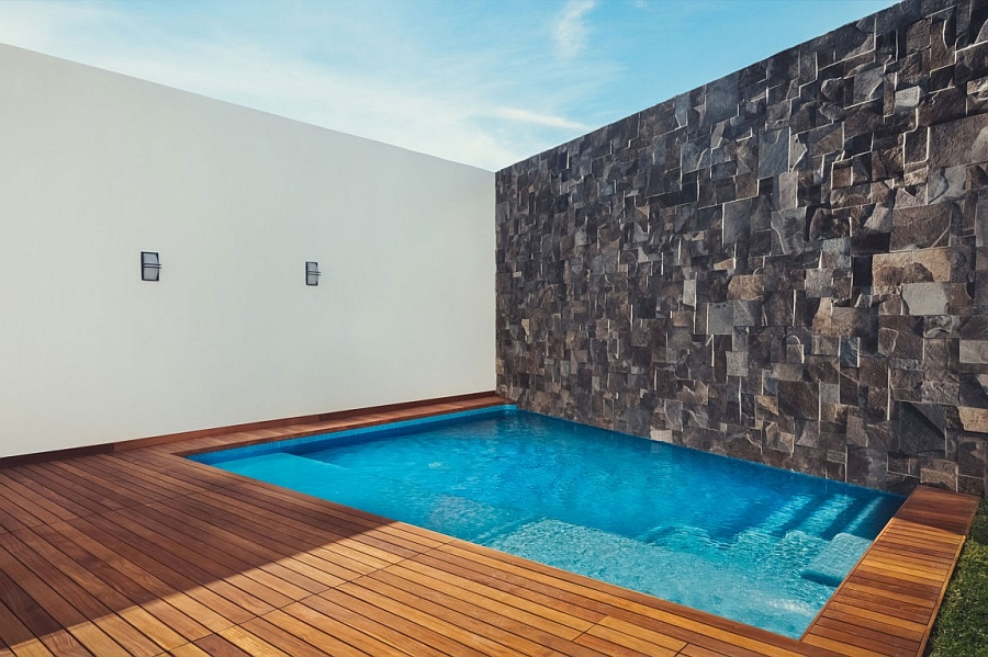 Private pool with a wooden deck and a stone wall on the side