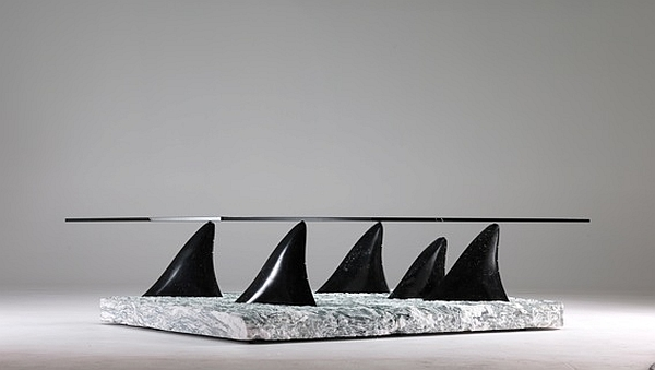 Smart side table with glass top and base shaped like dolphin fins