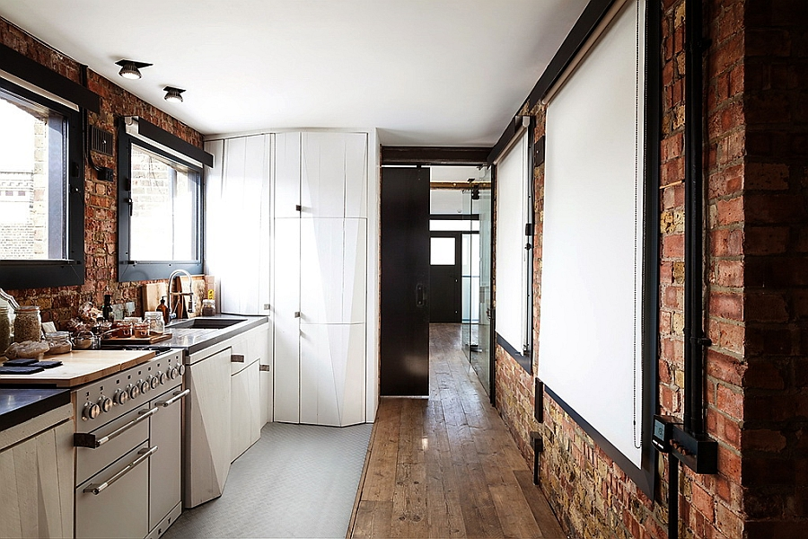 Spacious modern kitchen with exposed brick walls linking the reception and the bedroom