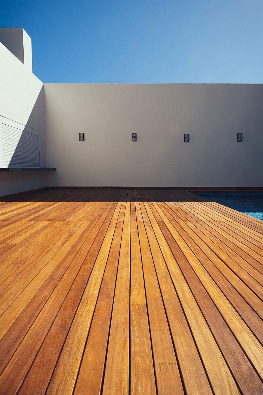 Spacious wooden deck next to the pool