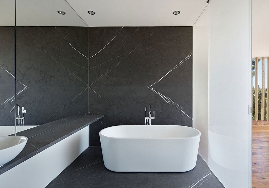Standalone bathtub in white placed in front of a dark backdrop