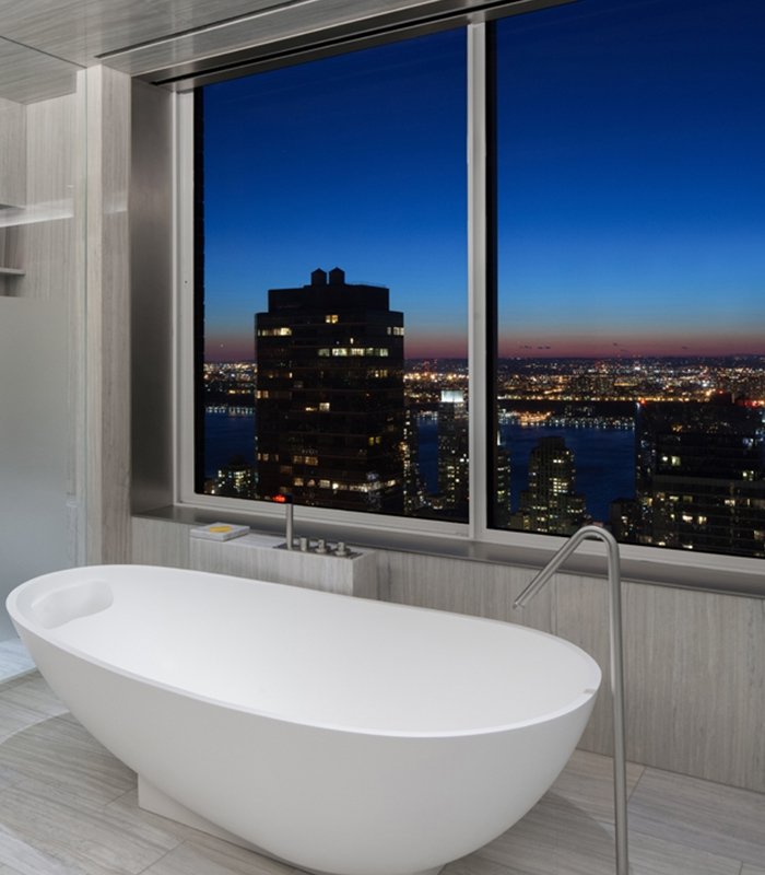 Standalone bathtub placed next to the window with city skyline views