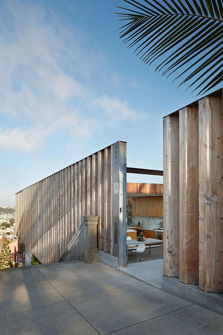 Terrace dining space and kitchen concealed by the giant solid wood louvers