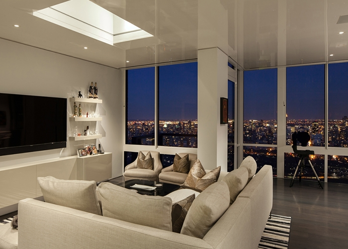 View of the living room at night with the bright lights of NYC Skyline in the backdrop