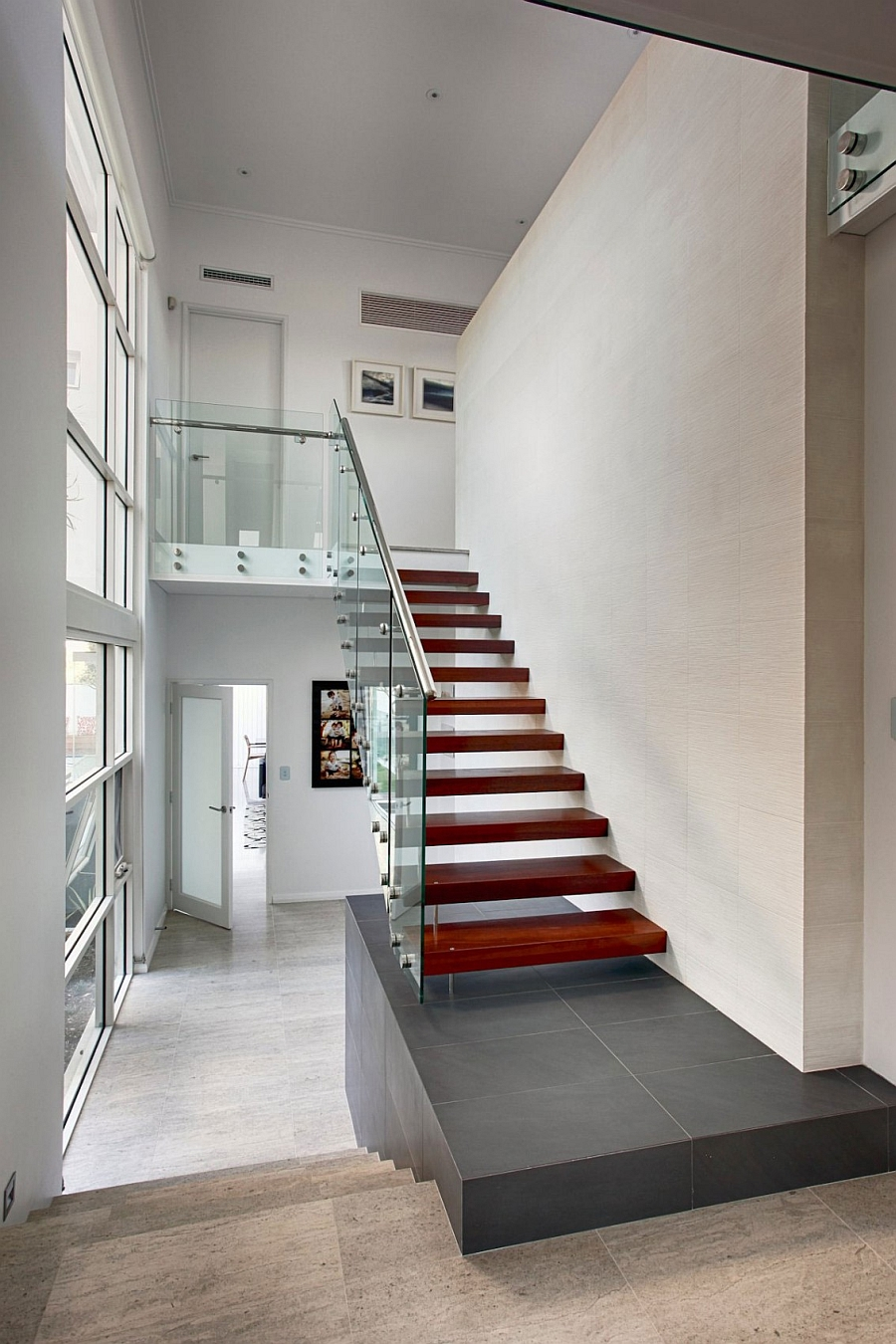 Wooden staircase with glass and steel railing