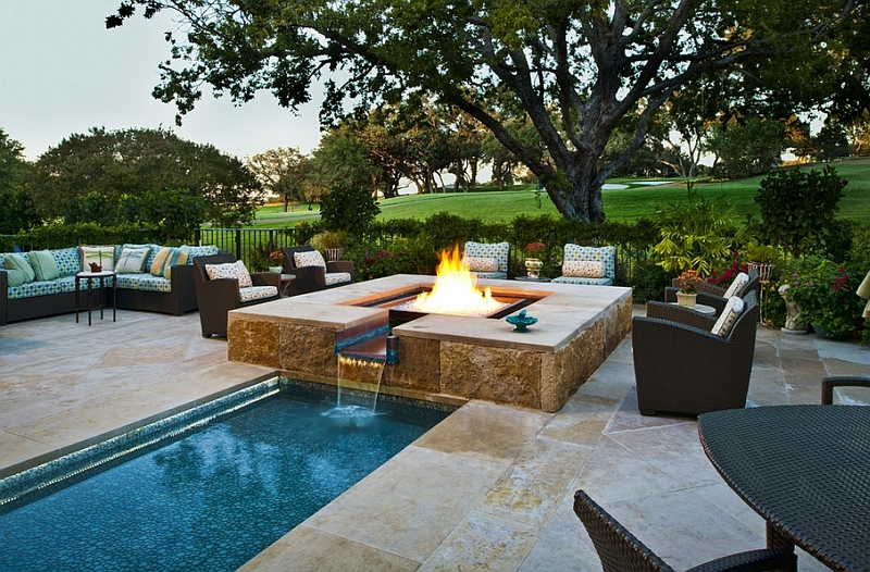 A cool water feature and fireplace that complements a larger pool perfectly