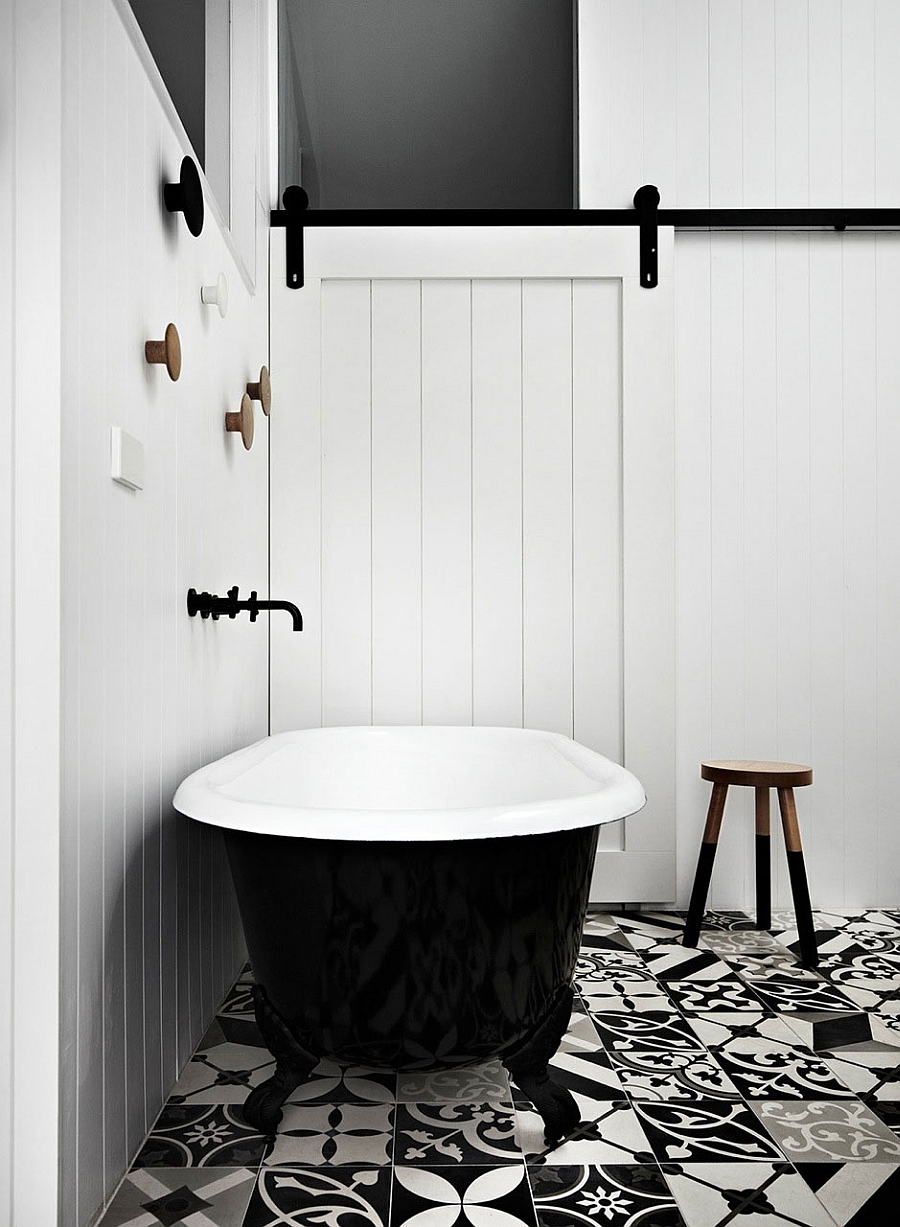 Black standalone claw-foot bathtub in the chic black and white bath