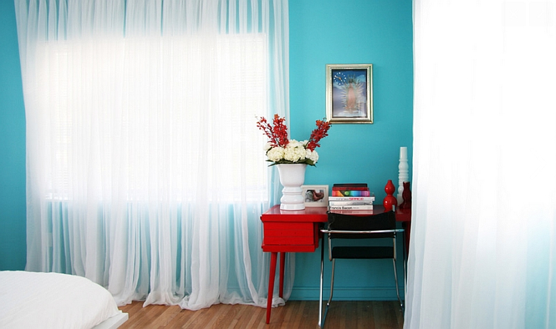 Breezy white sheer curtains give the red and turquoise bedroom an accentuated summer vibe