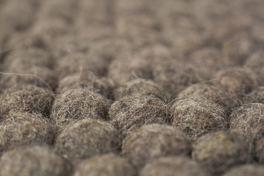 Closer look at the raw earth felt ball rug
