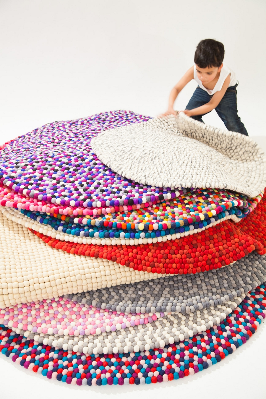 Colorful pile of felt ball rugs crafted from the finest wool