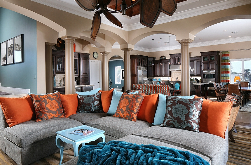 Comfy sectional filled with orange and blue throw pillows