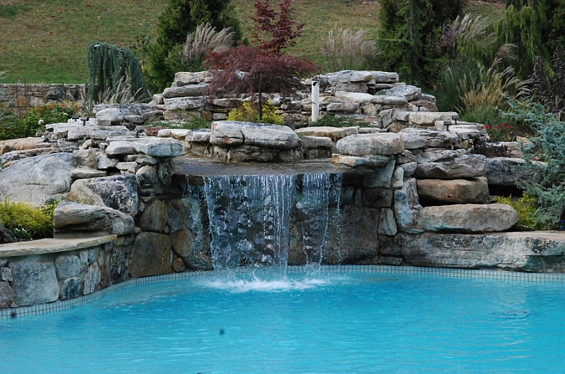Custom large scale swimming pool with a natural waterfall feature
