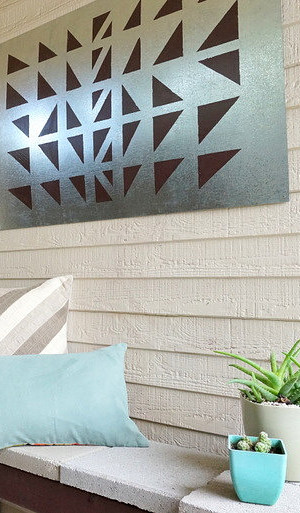 DIY outdoor wall art with a cinderblock bench