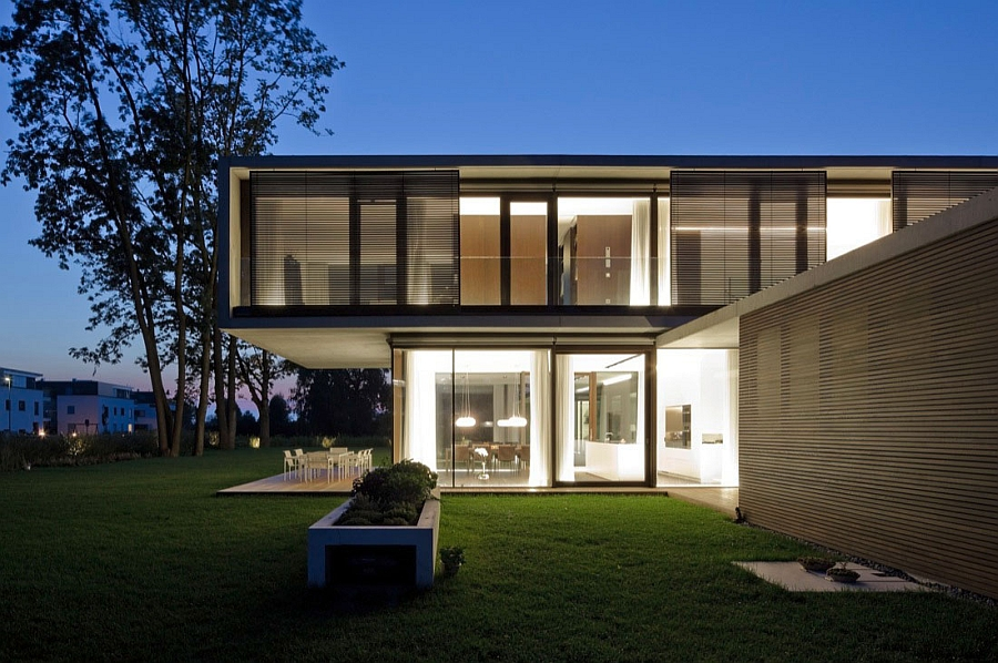 Dazzling illumination indoors also enlivens the backyard thanks to the glass walls